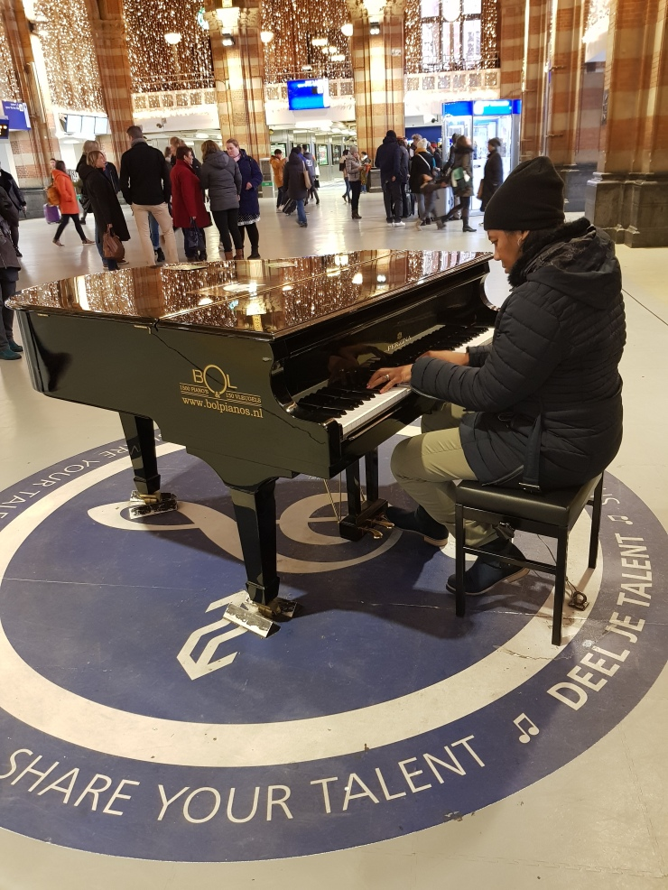Pauline, member of Cafemnee, plays on a public piano located in Amsterdam